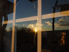 磨いたガラスに映る沈む太陽 テーブルの向こうの棚に夕日が当たり.jpg